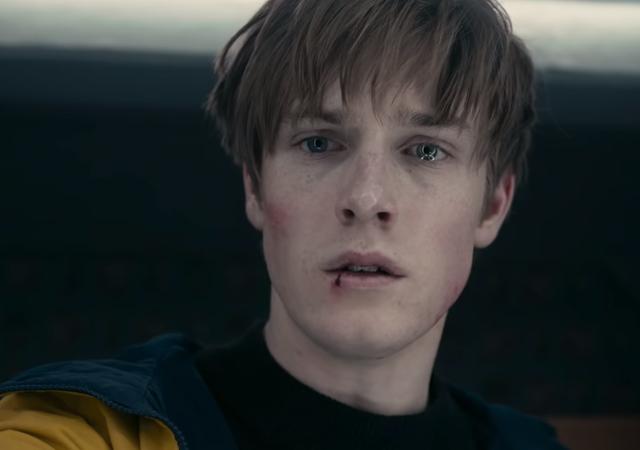 Trilogia Dark, imagem de jonas com a boca machucada e usando o casaco amarelo.