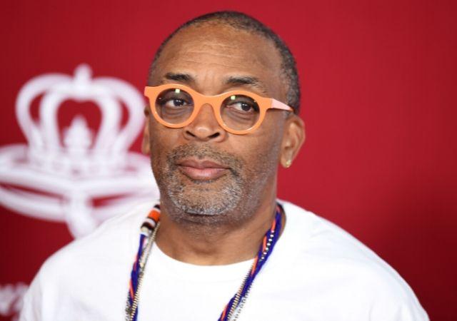 Spike Lee com blusa branca colar roxo e óculos laranja