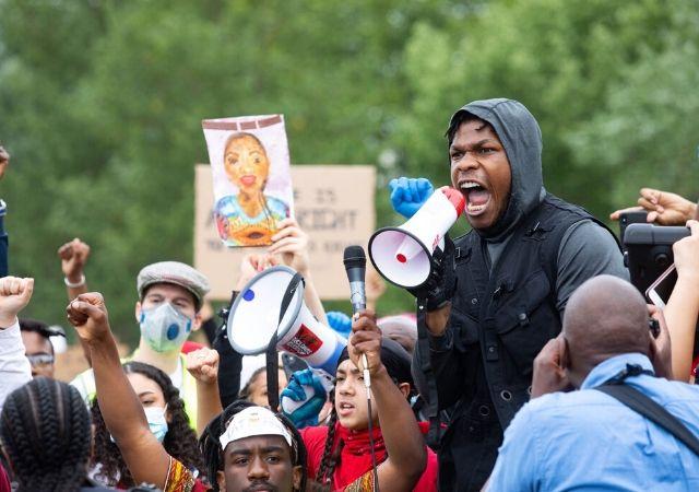 John Boyega discursa em mega fone durante manifestação