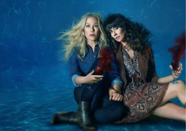 Atrizes da série Dead To Me, Christina Applegate e Linda Cardellini, embaixo d'água segurando uma taça de vinho.