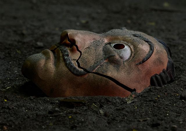 Máscara no chão quebrada ao meio, bem suja também. Imagem utilizada como o cartaz de anúncio da 5ª e última parte de La Casa de Papel