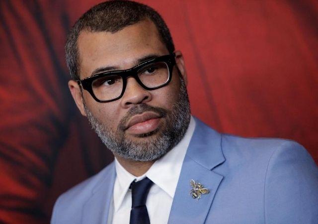 Jordan Peele sério com óculos de grau preto e terno azul, blusa branca e gravata preta
