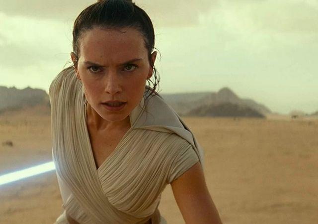 Protagonista de Star Wars olha para a câmera com semblante sério, segura seu sabre de luz e veste roupa bege