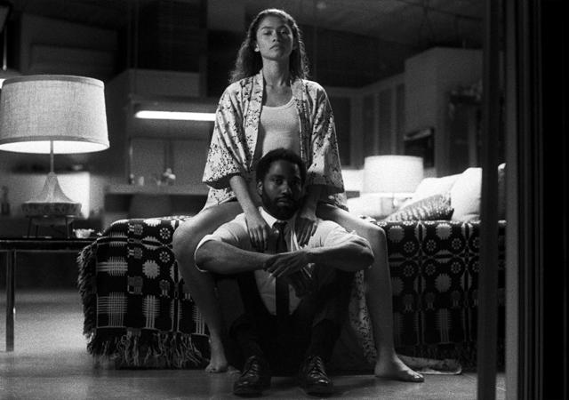 Imagem promocional de Malcolm & Marie, com uma mulher sentada na cama e um homem sentado no chão.