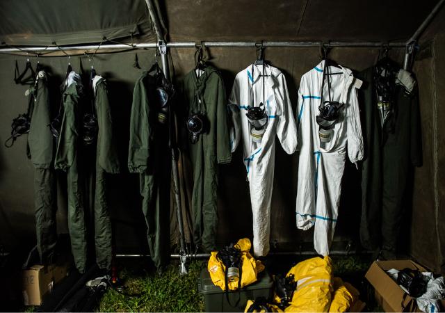 Macacões e máscaras de segurança pendurados em um armário